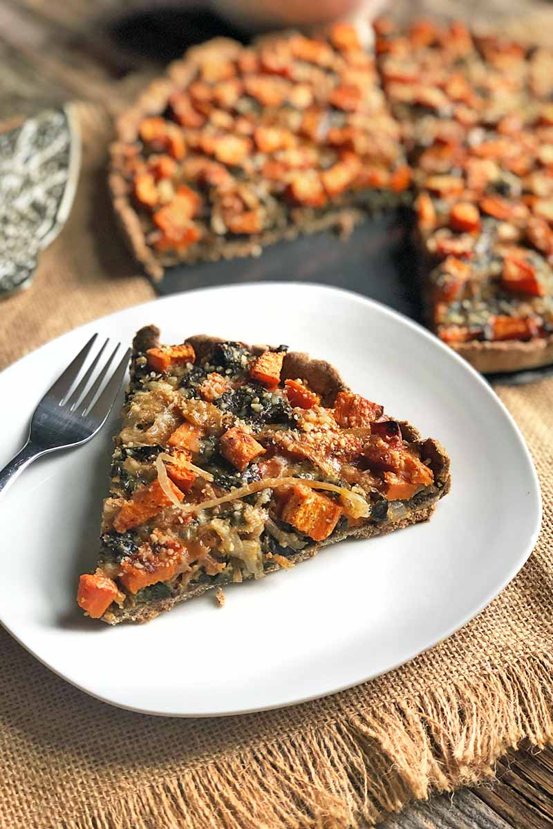 Vertical image of a slice of Swiss chard and sweet potato tart in a buckwheat crust on a white plate with a fork, with more of the dish in a metal pan in the background, on a piece of burlap with fringe on top of a wooden table, with sprigs of fresh thyme.