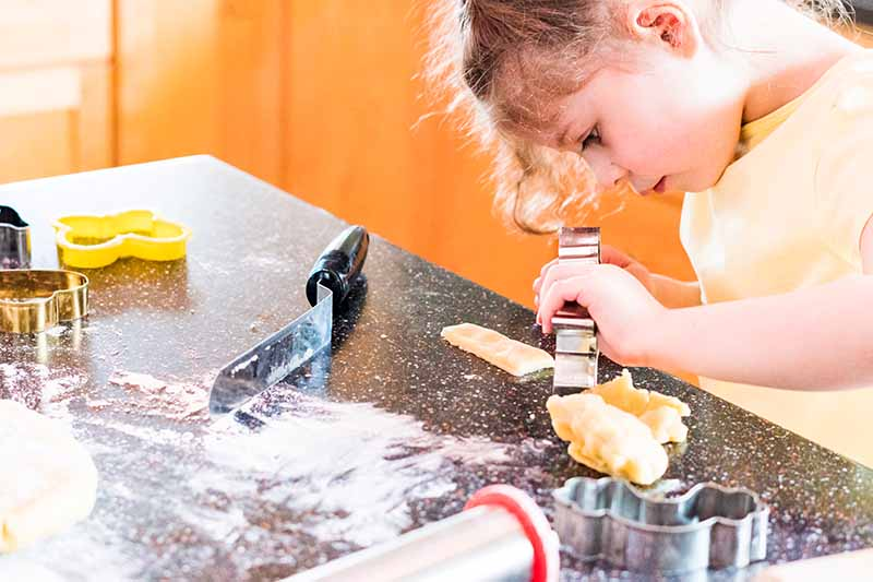 A little girl in a yellow shirt is preparing to cut a piece of dough with a metal cookie cutter, on a black countertop with scattered flour and other cooking implements, with an orange background.