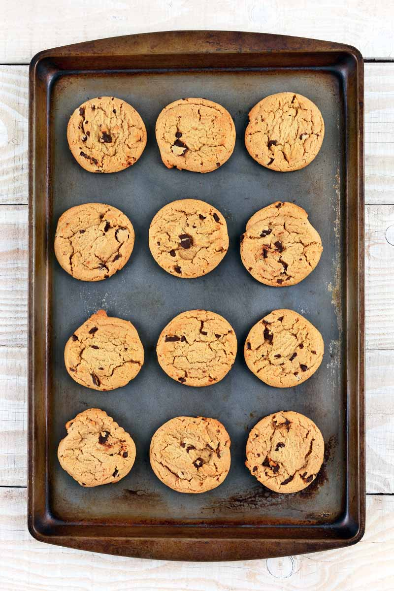 Vertical overhead image of twelve chocolate chip cookies arranged in rows of three each on a worn and used rimmed metal baking sheet, on a white painted wood surface with visible grain.