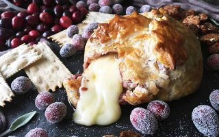 Horizontal image of pastry with melted cheese oozing out, surrounded by various accoutrements.