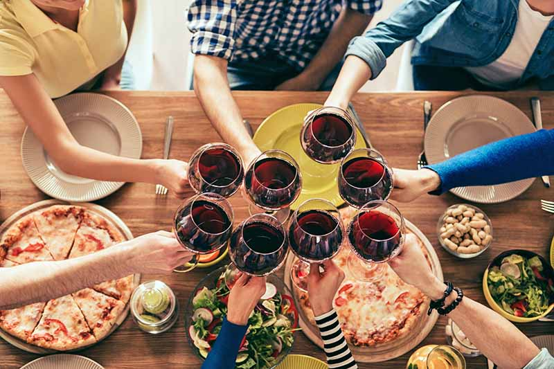 Horizontal overhead image of eight people clinking their glasses of red wine together over the center of a table laden with pizza and salad, with just the arms and torsos of the seated women visible, with ceramic plates on a brown wood surface.