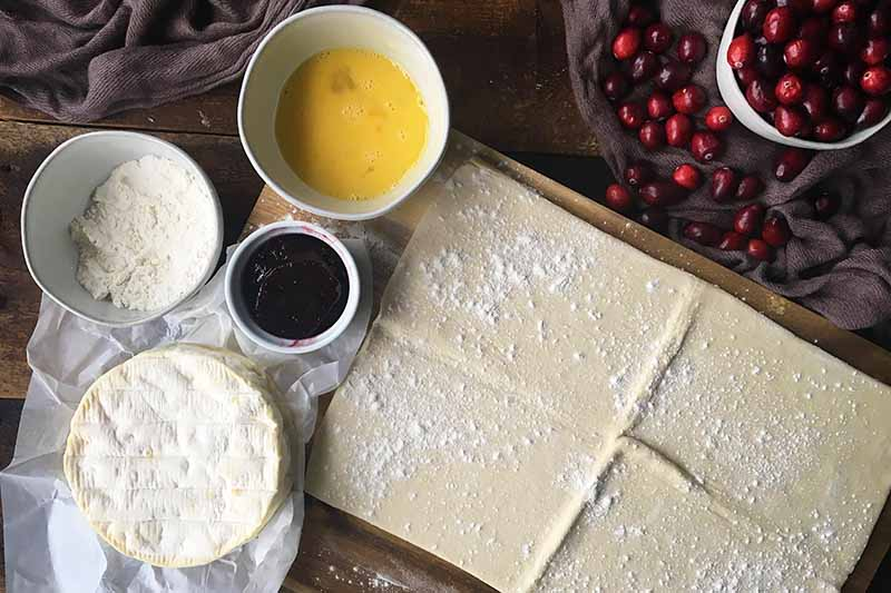Horizontal image of a rectangle of pastry, a wheel of brie, and bowls of eggs, flour, jam, and cranberries.
