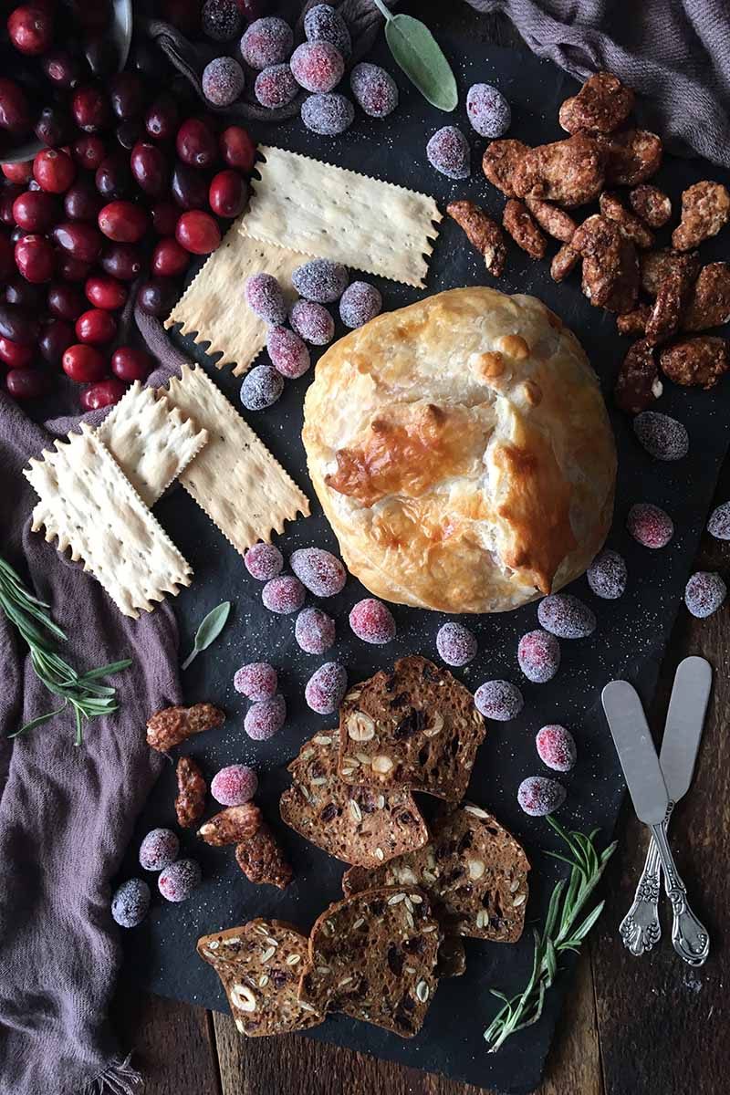 Vertical top-down image of a circular baked good on a slate with crackers, fruit, herbs, nuts, and knives.