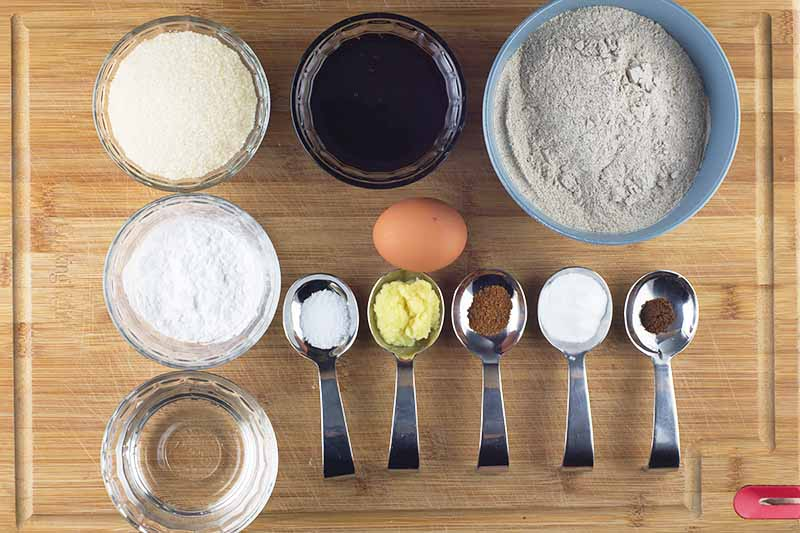 Overhead horizontal image of a blonde wood cutting board topped with bowls of various sizes and metal measuring spoons filled with buckwheat flour, arrowroot powder, molasses, baking soda, salt, melted coconut oil, and spices, with a brown egg.