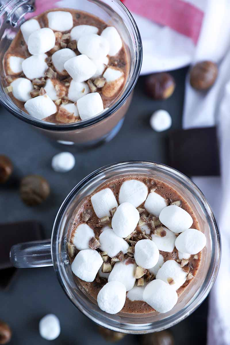 Vertical overhead image of two mugs of homemade chestnut hot chocolate topped with mini marshmallows, with scattered ingredients on a gray surface, and a white and red striped dish towel at the top and right of the frame.
