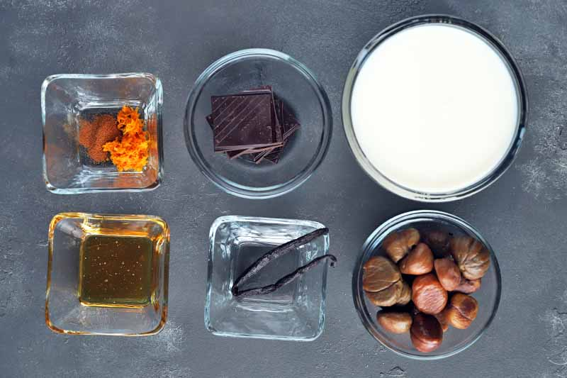 Overhead horizontal image of three round and three square glass bowls of orange zest, honey, pieces of dark chocolate, a vanilla bean, milk, and roasted chestnuts, on a gray surface.