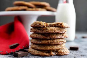 Horizontal image of a stack of thin, dark cookies next to a red towel and white cake stand.