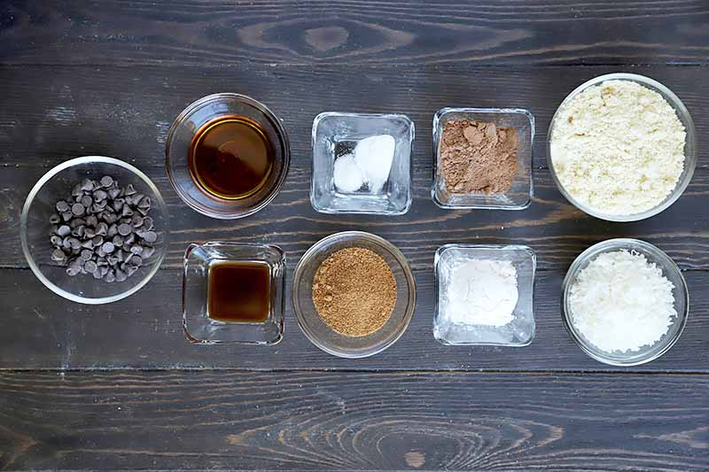 Horizontal overhead image of small round and square glass bowls of dark chocolate chips, maple syrup, vanilla extract, salt, cocoa powder, almond meal, shredded coconut, tapioca flour, sucanat, and baking soda, on a dark brown wood surface.