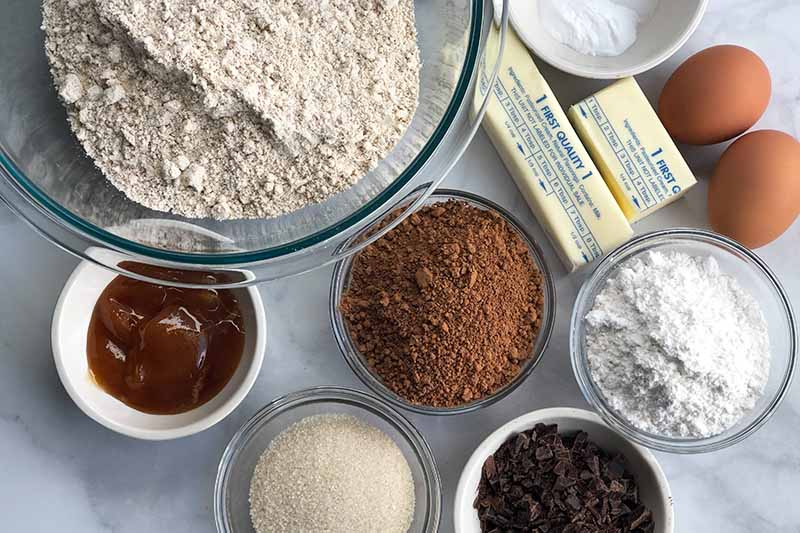 Horizontal overhead closely cropped image of a glass bowl of spelt flour, and smaller glass and ceramic bowls of honey, cocoa powder, powdered sugar, granulated sugar, and chocolate chips, with a stick and a half of butter wrapped in waxed paper and two brown eggs, on a white marble surface with gray veins.