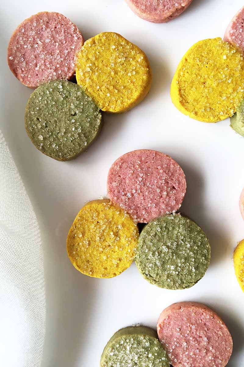 Vertical top-down image of pink, yellow, and green circular treats sprinkled with sugar on a white surface.