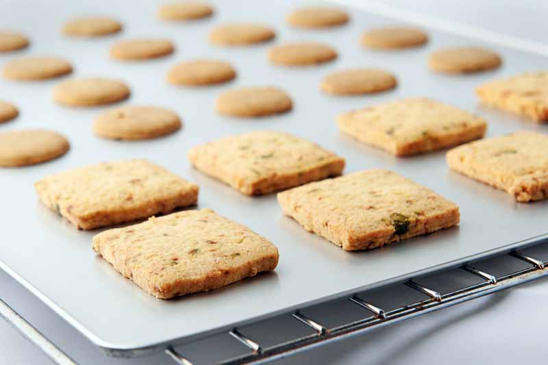 Horizontal image of square and round shortbread cookies on a rimless baking sheet on top of a metal cooling rack, selective focus, on a gray surface with a white background.