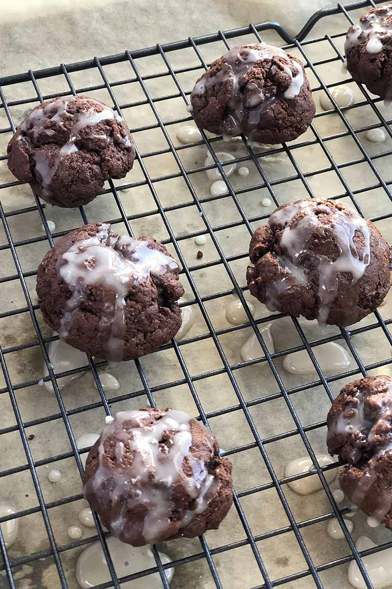 Vertical oblique overhead image of cookies 'n cream baked goods with white glaze on top, on a cooling rack on top of a beige surface.