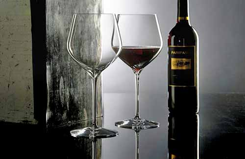 Two red wine glasses, one filled and one empty, in a dark room against a partition wall on a dark brown table, with a bottle of wine, in low light.