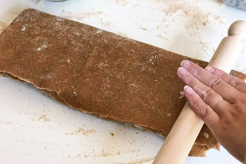 Horizontal image of a hand on a wooden rolling pin on top of sheets of a dark brown floured dough.