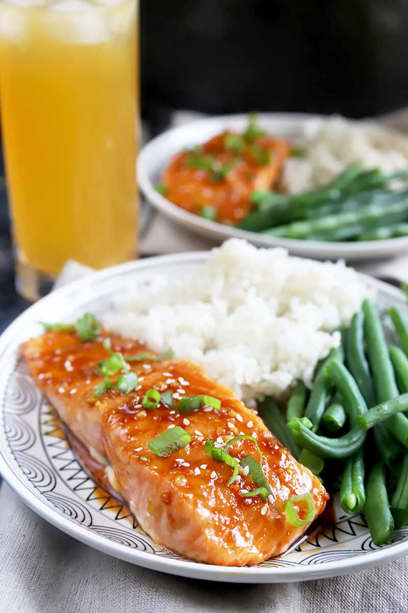Horizontal image of two plates with baked fish fillets, green beans, and white rice next to a tall glass of an orange beverage.