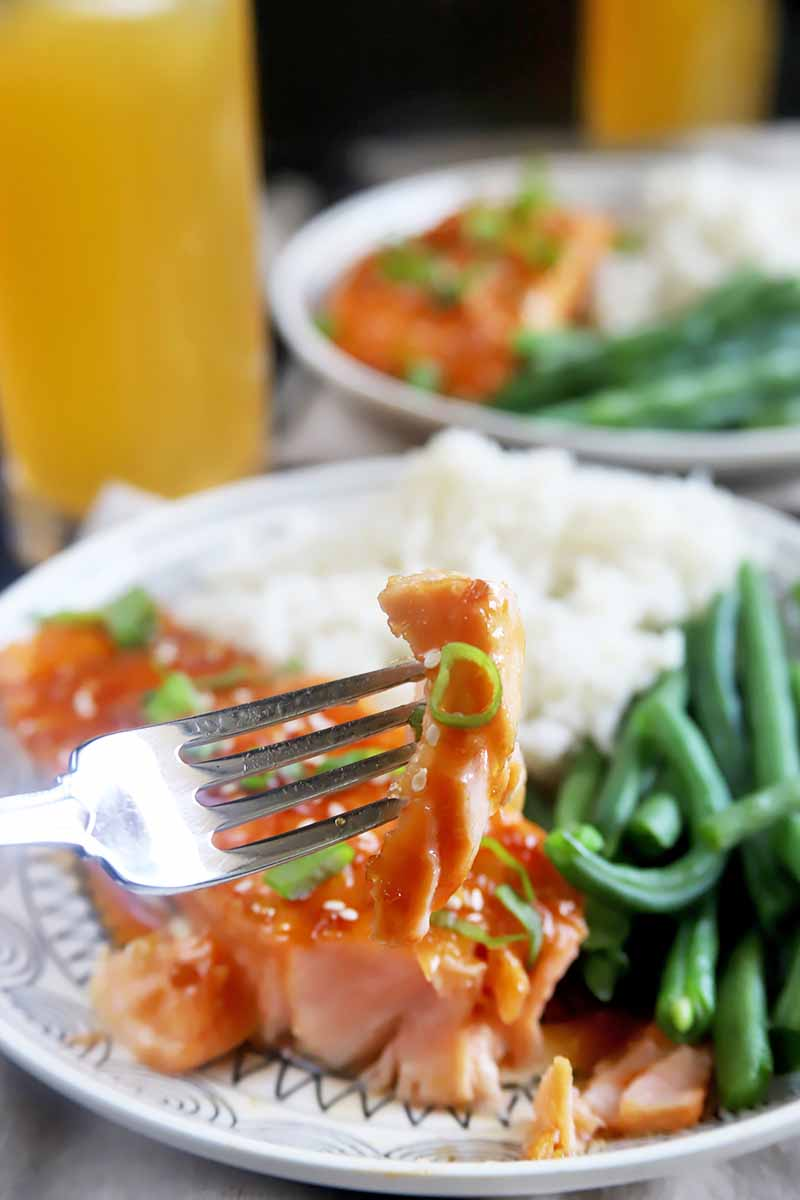 Vertical image of a fork holding a piece of pink fish over a plate with white rice and green beans and an orange beverage.