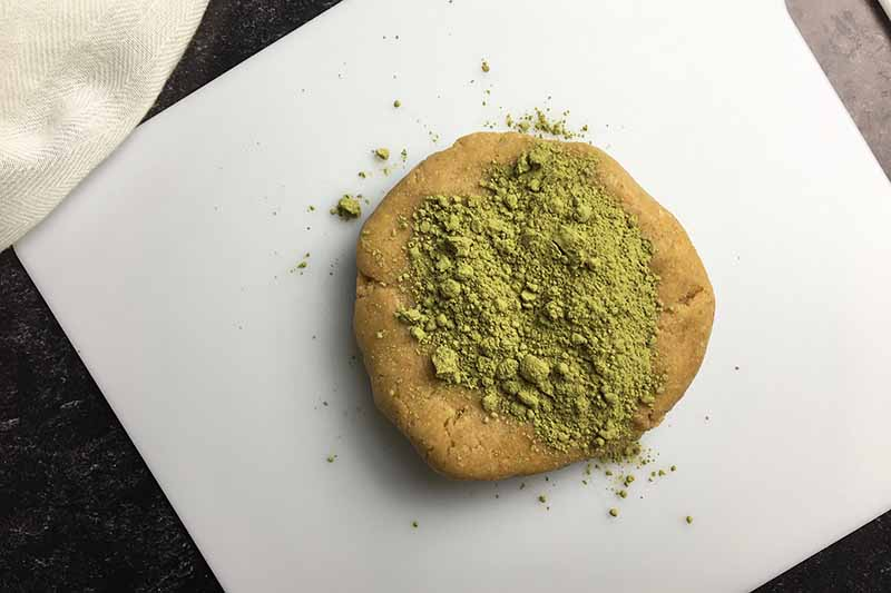 Horizontal image of a tan disc of dough with matcha green powder on top on a white cutting board.