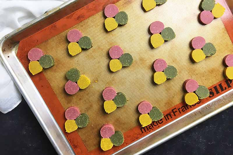 Horizontal image of a baking sheet with a silicone mat, with slices of tri-color unbaked cookie pieces arranged in rows.