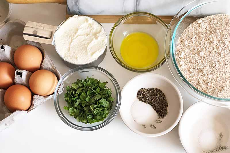Horizontal image of assorted wet and dry ingredients in bowls next to brown eggs and a marble rolling pin.
