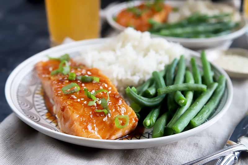 Horizontal image of two white plates with green beans, rice, and fish fillets topped with green onions and sesame seeds.