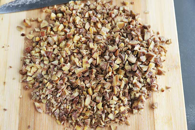 Overhead horizontal closely cropped image of finely chopped roasted chestnuts with a knife on a wooden cutting board, on a gray surface.
