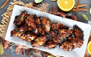 Horizontal overhead image of a white rectangular ceramic platter of homemade grilled wings, on a gray surface on a multicolored cloth with fringe, with scattered pieces of cut citrus, bay leaves, and whole cinnamon sticks.
