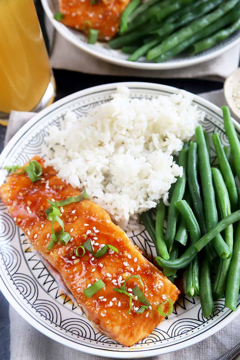 Vertical image of a plate with a baked fish fillet, green beans, and cooked white rice.