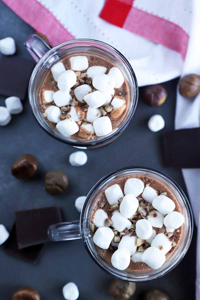 Vertical overhead image of two glass mugs of a homemade warm chocolate beverage topped with miniature marshmallows, on a gray surface with scattered pieces of chocolate, marshmallows, and whole roasted chestnuts, with a red striped white kitchen towel to the right, on a dark gray surface.