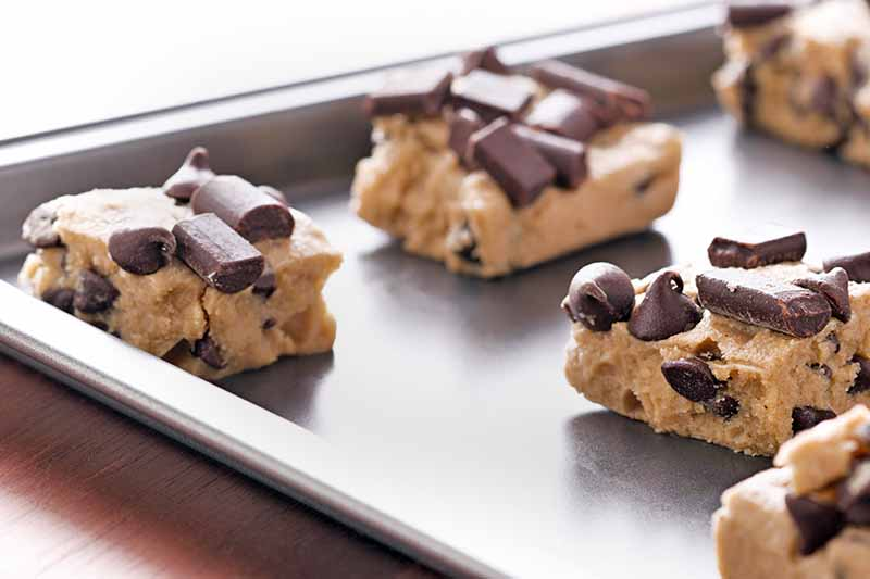 Horizontal image of square portions of cookie dough topped with chocolate chips and chunks, arranged on a rimmed metal baking sheet, on a beige countertop with a white brightly lit background.