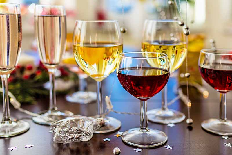 Horizontal image of three pairs of champagne, white, and red wine glasses, filled with the appropriate beverages, on a brown table with plastic and foil star decorations.