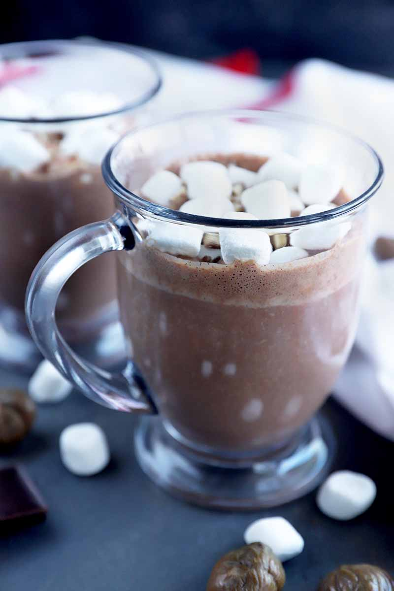 Vertical image of two clear glass mugs of hot chocolate, on a gray surface with scattered miniature marshmallows, pieces of dark chocolate, and whole roasted chestnuts, with a white cloth with red trim in soft focus in the background.