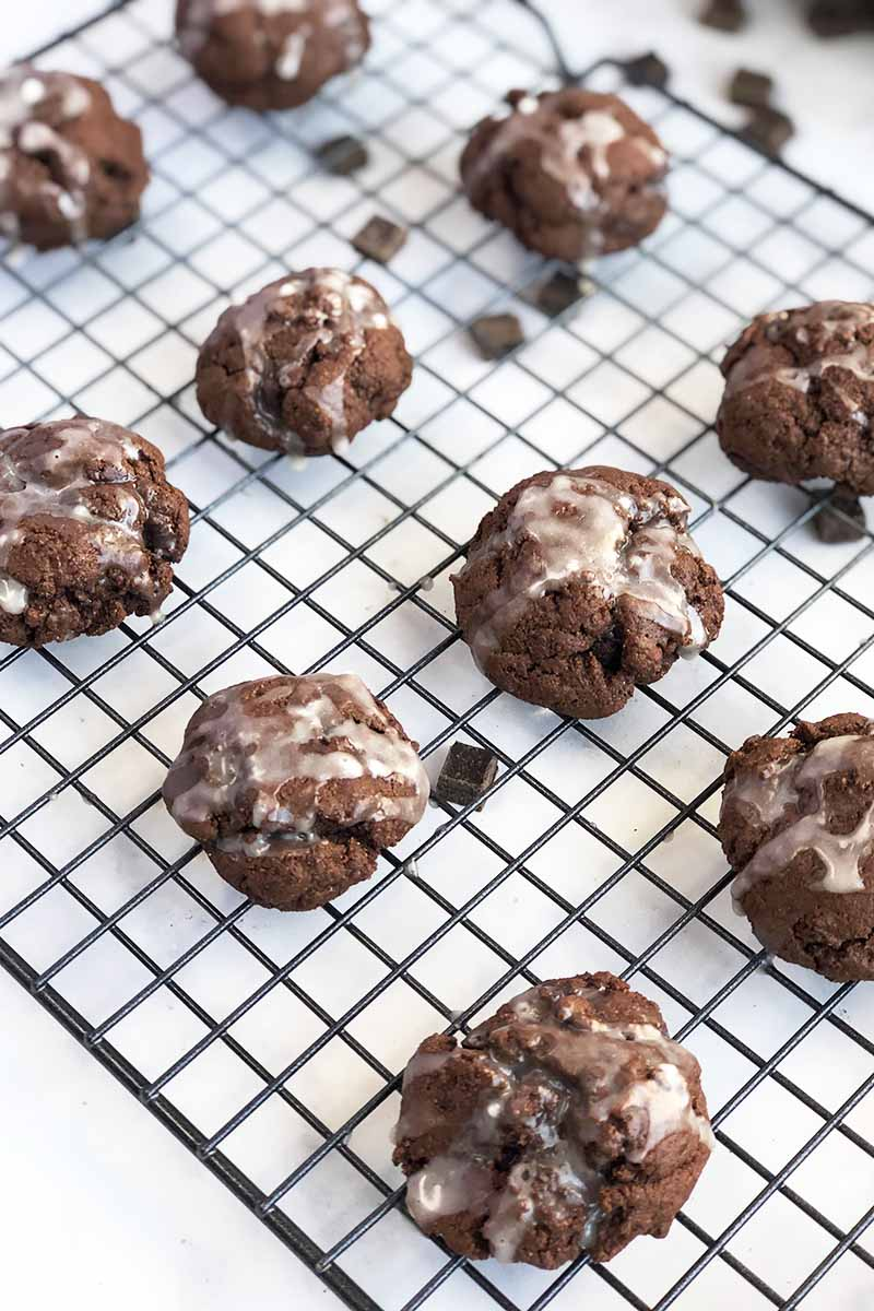 Vertical oblique overhead image of chocolate cookies with white glaze on top cooling on a wire rack, with a black backdrop and scattered chocolate chips.