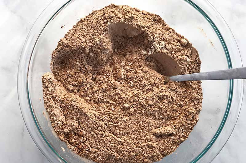 Overhead closely cropped horizontal image of a brown mixture of dry ingredients in a glass mixing bowl with a spoon, on a white background.