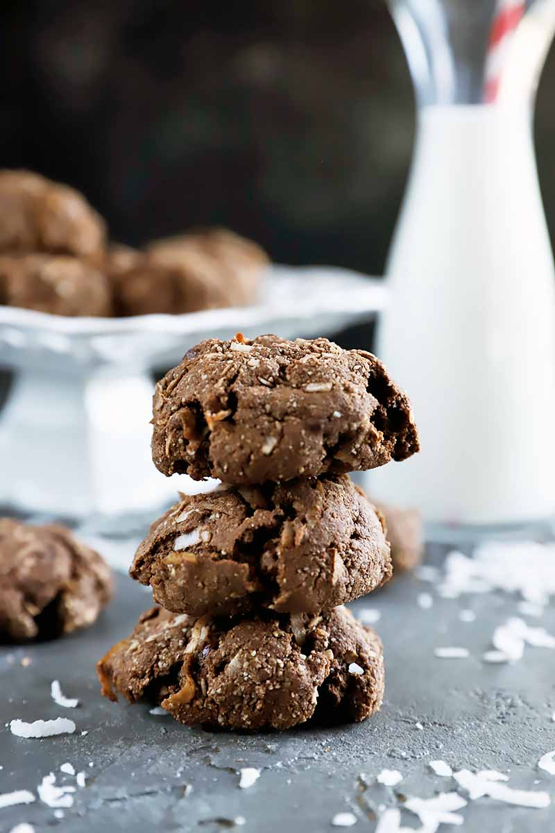 Vertical image of a stack of three gluten-free chocolate cookies, with more in the background on a gray surface topped with scattered pieces of shredded coconut, and on a white ceramic pedestal in soft focus in the background, beside a tall glass bottle of milk.