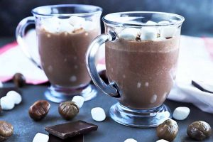 Horizontal image of two clear glass mugs with handles, filled with homemade hot chocolate, on a gray surface with scattered pieces of a dark chocolate bar, whole roasted chestnuts, and mini marshmallows, with a white kitchen towel with red trim in the background in soft focus.