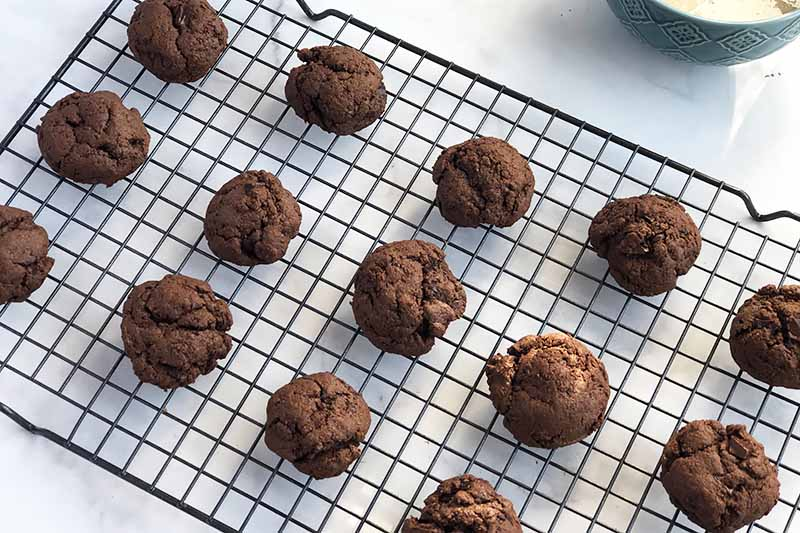 Round mounded chocolate cookies arranged in three rows, cooling on a wire rack on a white kitchen countertop.
