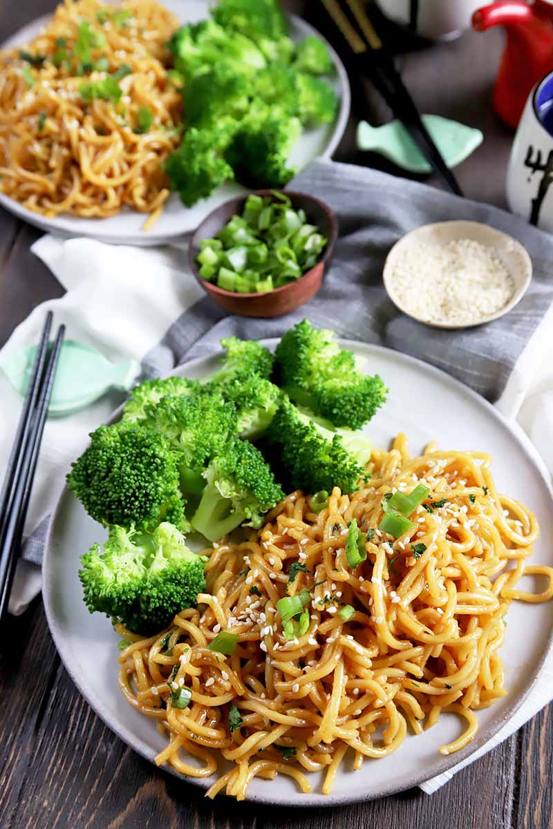 Vertical image of two white plates with seasoned pasta and broccoli florets on towels next to chopsticks, chopped spring onions, and a white garnish.