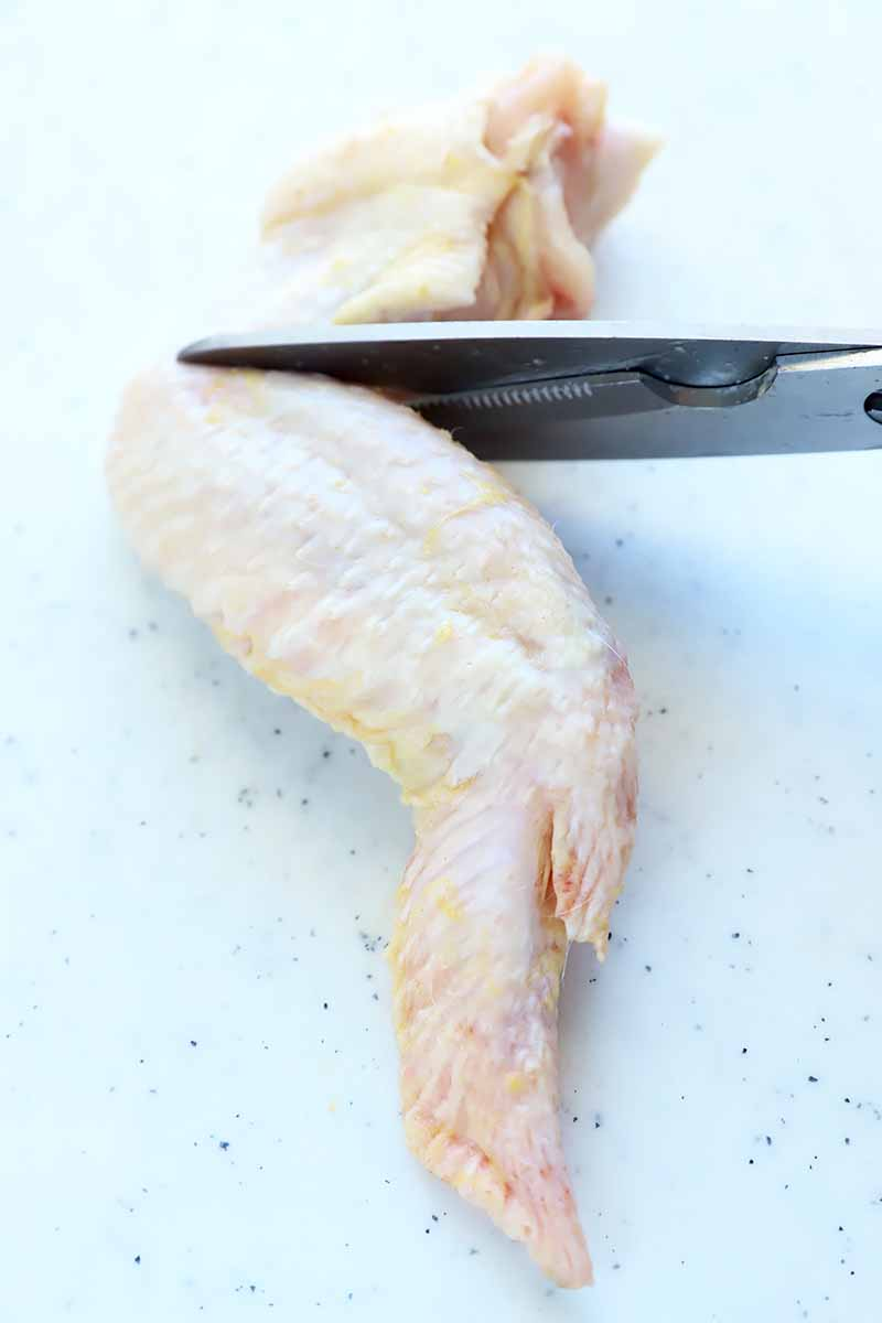 Vertical image of kitchen shears cutting a whole raw poultry piece.