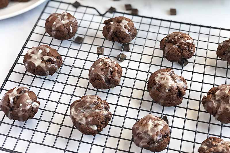 Horizontal oblique overhead image of cookies 'n' cream chocolate treats with white glaze on top, cooling on a wire rack on a white surface.