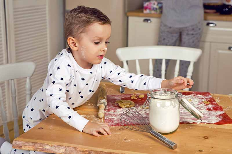Horizontal image of a boy in black and white pajamas, peering into a glass canister of flour, leaning on a wood kitchen table with rolling pin, whisk, cutting board, and other implements for making cookies, dusted with flour, with flour on his nose and cheek, with two white chairs, and a kitchen counter with a woman in the background in gray pajamas standing in front of it, with only her legs and torso visible.