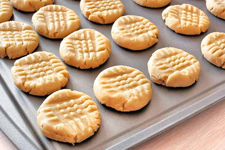 Horizontal closely cropped oblique overhead image of peanut butter cookies with a grid pattern on top made with a fork, arranged in rows on a metal sheet pan, on a beige countertop.