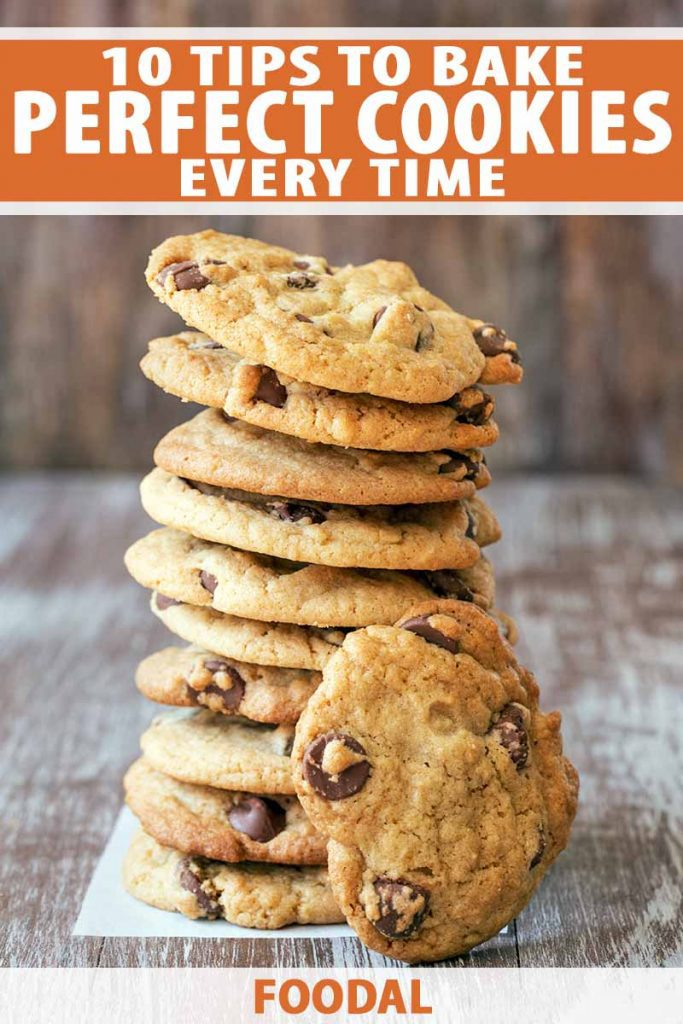 Vertical image of a stack of ten homemade chocolate chip cookies with another propped up in front of the stack, on a small rectangle of parchment paper on top of a weathered whitewashed wood surface, printed with orange and white text at the top and bottom of the frame.