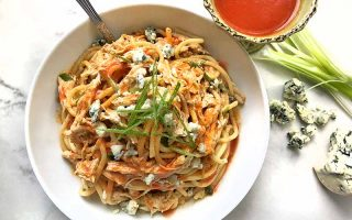 Horizontal overhead image of a white bowl of pasta with shredded chicken, Buffalo sauce, crumbled blue cheese, and sliced green onions, on a gray and white marble surface with a bowl of red sauce, scallions, and gorgonzola.