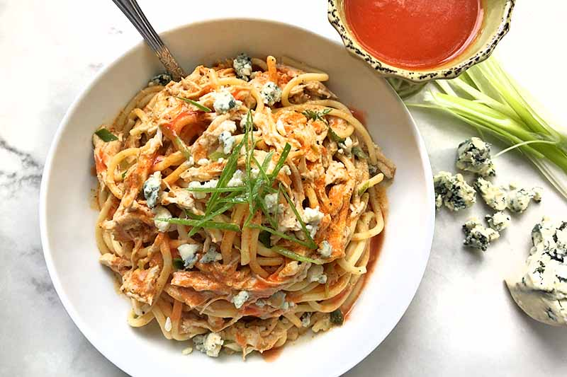 Horizontal overhead image of a white bowl of pasta with shredded cooked poultry, Buffalo sauce, crumbled blue cheese, and sliced green onions, on a gray and white marble surface with a bowl of red sauce, scallions, and gorgonzola.