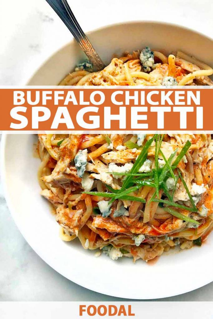Vertical overhead image of a white bowl of Buffalo chicken spaghetti, with green onions and crumbled blue cheese for garnish, on a white and gray surface, with a fork stuck into the bowl, printed with orange and white text near the middle and at the bottom of the frame.