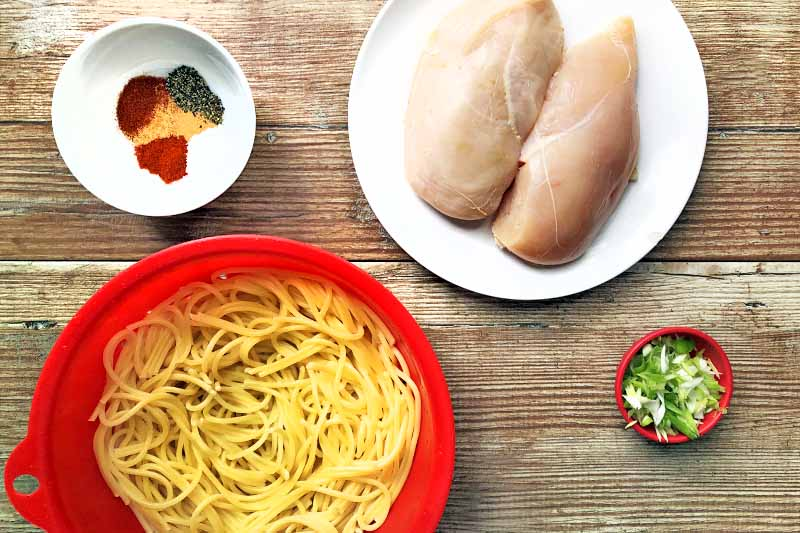 Overhead closely cropped horizontal image of a small white bowl of spices, two boneless skinless raw chicken breasts on a white plate, a terra cotta ramekin of chopped scallions, and a red plastic colander of cooked spaghetti, on a wood background.