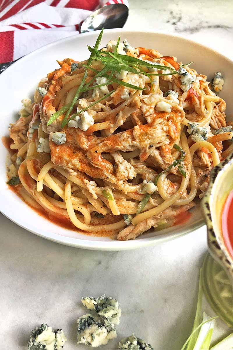 Vertical image of a white bowl of spaghetti with chicken, Buffalo sauce, crumbled gorgonzola, and thinly sliced scallions, on a gray surface with blue cheese, scallions, and a red and white cloth napkin topped with a spoon.
