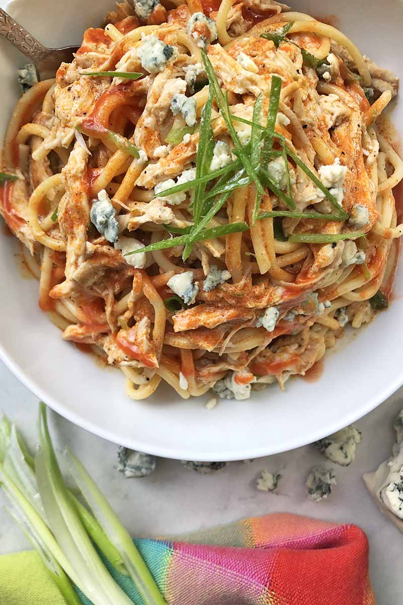 Vertical overhead closely cropped image of a white bowl of spaghetti with Buffalo chicken, crumbled blue cheese, and scallions at the top of the frame, with a folded multicolored cloth napkin, cheese, and whole green onions at the bottom.