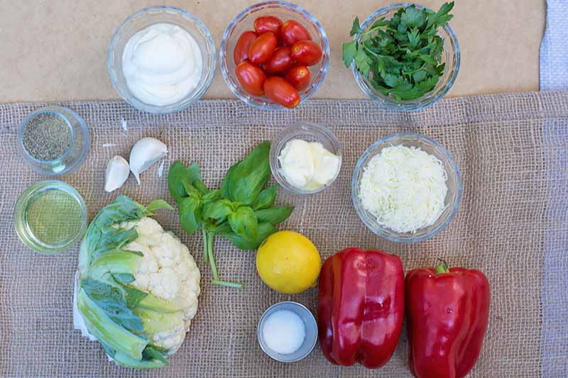 Horizontal image of assorted vegetables, herbs, cheese, and seasonings on a tan surface.