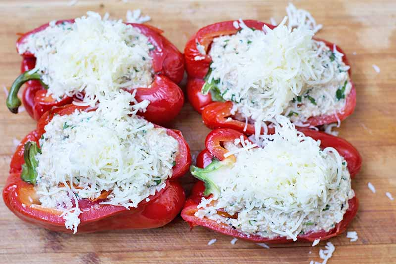 Horizontal image of cheese-topped stuffed peppers.